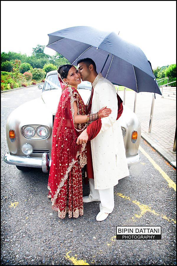 couple portraits by photographer on a rainy day at Oshwal Centre Potterbar