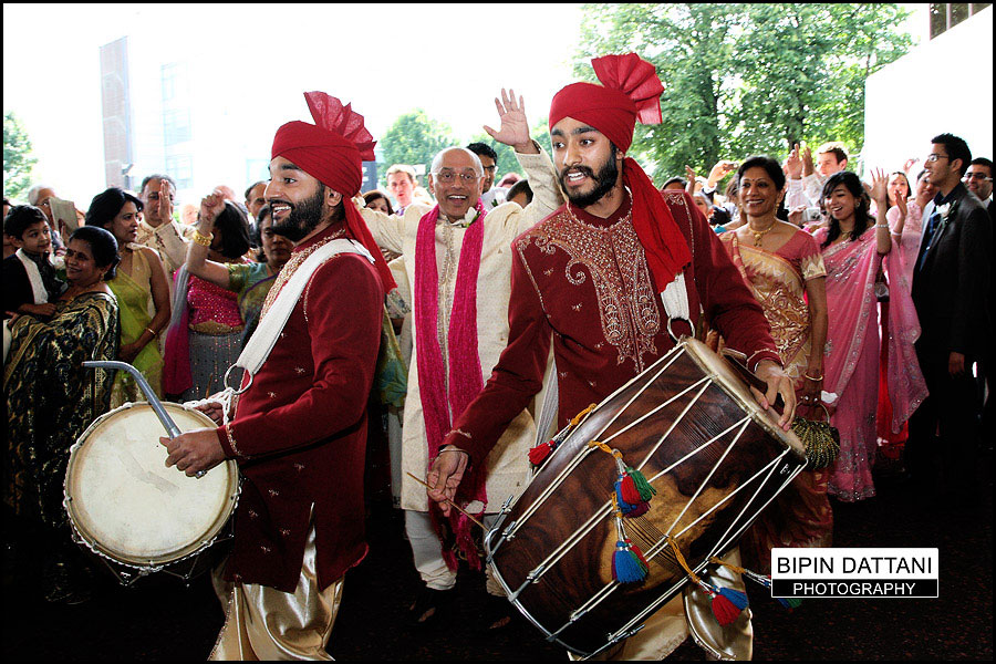 combined indian wedding photography and videography packages vendors capturing traditional indian baraat groom's entrance with dhol players