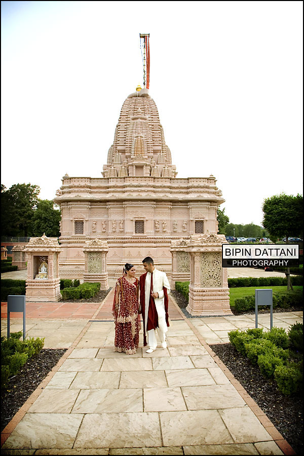 bride & groom oshwal centre temple as background