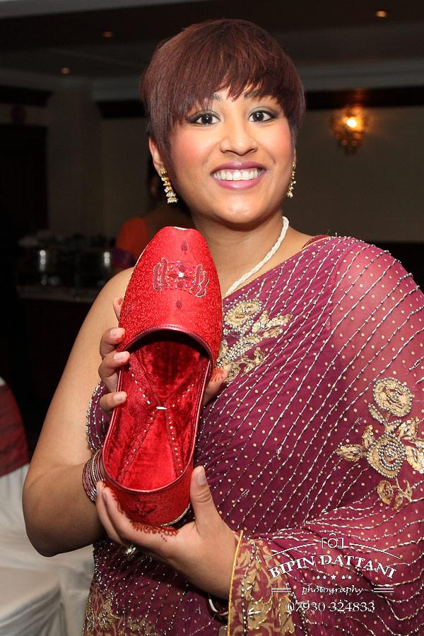 wembley asian wedding photographer capturing the groom's stolen shoe custom