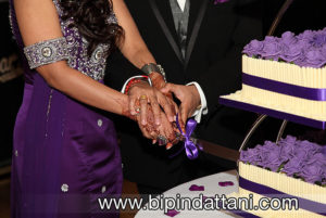 A close-up photo od couple cutting wedding cake