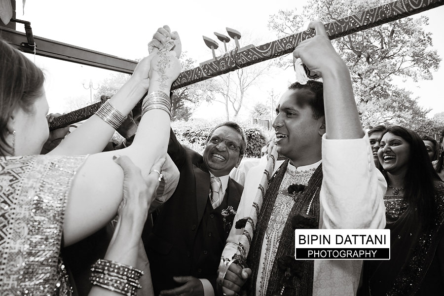 candid indian wedding photographer capturing grooms entrance in Kent
