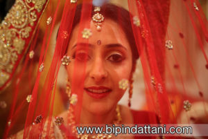 indian bride getting ready with makeup artist and wedding dress photo by Bipin Dattani