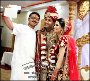 Hindu wedding priest Ketanbhai Mehta taking selfie with bride and groom Nisha & Vinesh at Stanmore Temple for facebook and instagram marketing