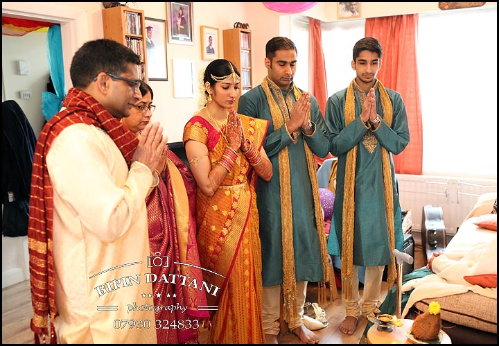 south indian tamil bride saying prayers with family before leaving home