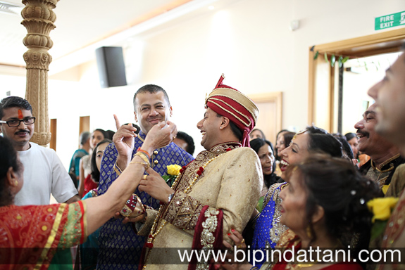 candid gujarati wedding photography at groom's entrance ritual of nose pinching by brides mother