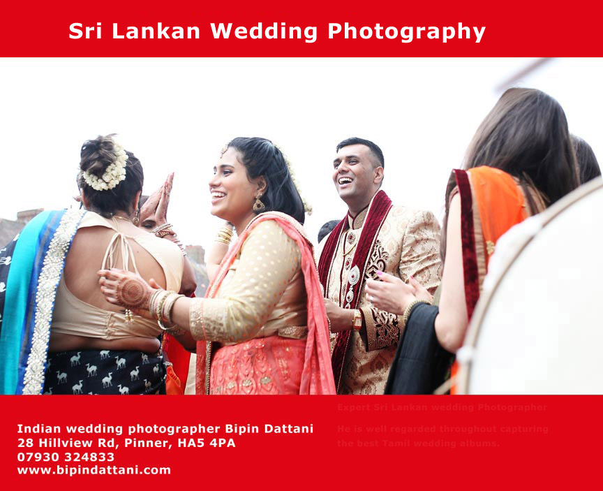 smiling sri lankan tamil groom with guests in sari making a fantastic for his wedding ceremony.